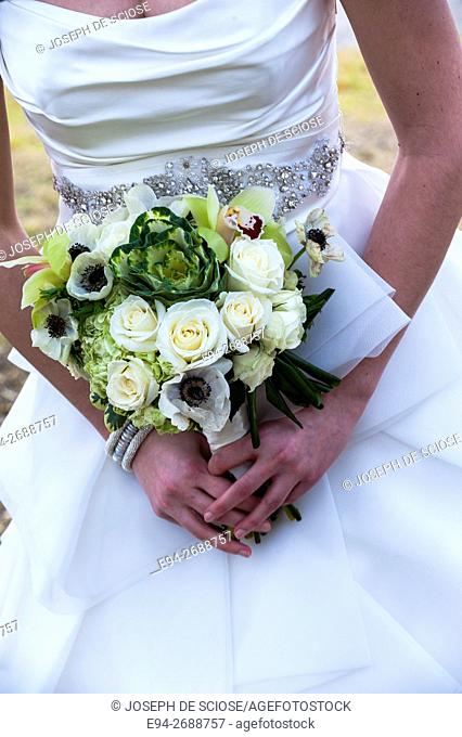 A close up of a bridal bouquet in the hands of a bride