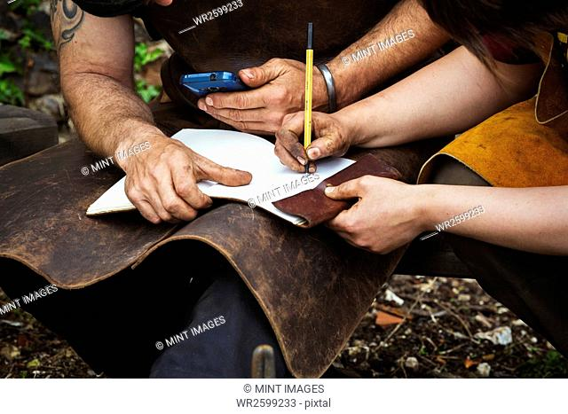 Man and woman, blacksmiths wearing aprons writing into a notebook sat in a garden