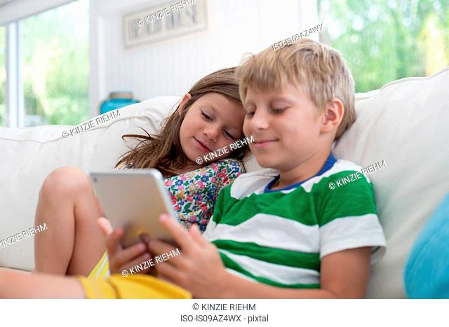 Brother and sister on sofa using digital tablet
