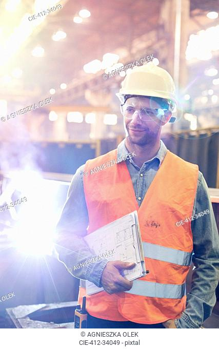 Steel worker with clipboard in factory
