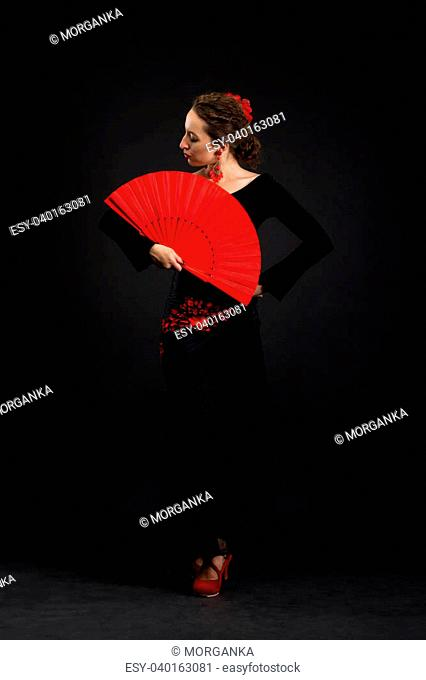 Flamenco dancer in black dress with red fan