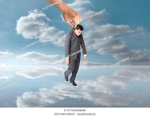 Big hand holding a businessman by his jacket over water