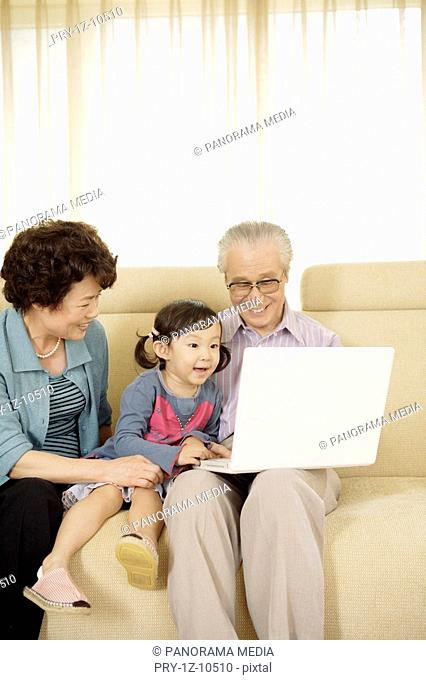 Senior couple and granddaughter playing with laptop in sofa