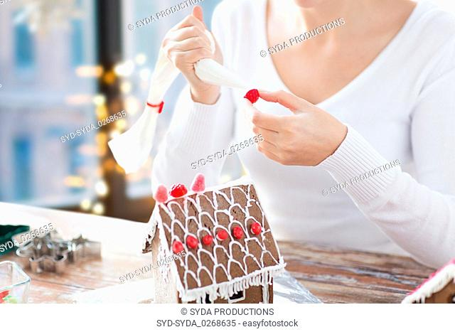close up of woman making gingerbread house