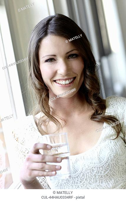 Smiling woman drinking glass of water