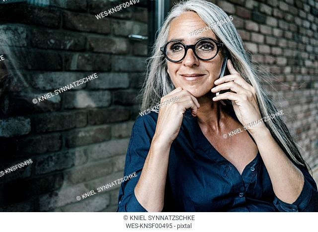 Smiling woman with long grey hair on cell phone