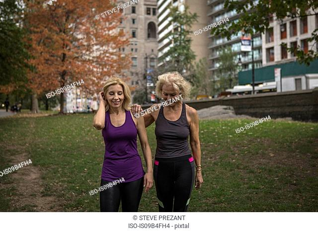 Two mature female friends training in park, walking
