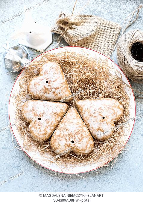 Overhead view of heart shaped gingerbread biscuits on straw covered plate