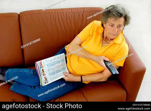 Seniorin auf Couch mit TV-Fernbedienung