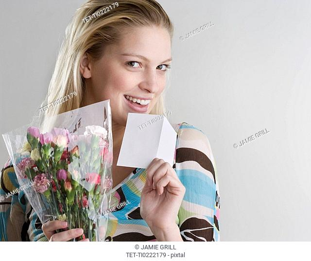 Woman holding flowers and card