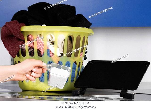 Woman putting detergent into a washing machine
