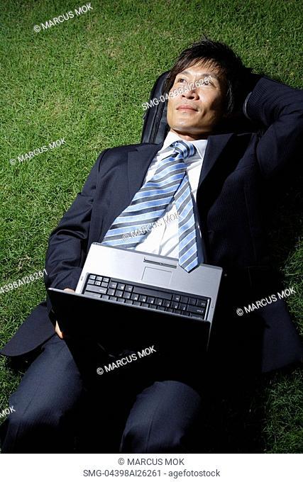 Businessman resting on grass, open laptop