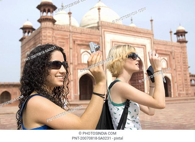 Side profile of two young women taking a picture in front of a mausoleum, Taj Mahal, Agra, Uttar Pradesh, India