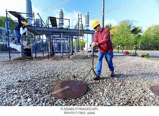 Power engineer accessing manhole cover at high voltage power distribution station