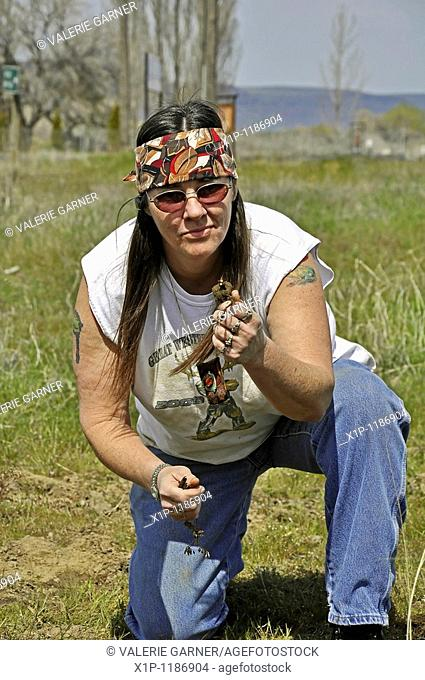 his mature Native American Indian woman with long hair and a headband has dug and is showing Camas sweet potatoes roots Camas is a traditional Native American...