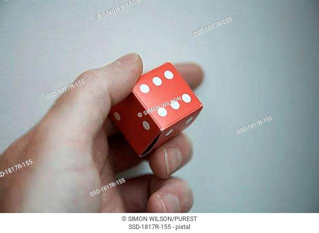 Hand holding red cardboard dice