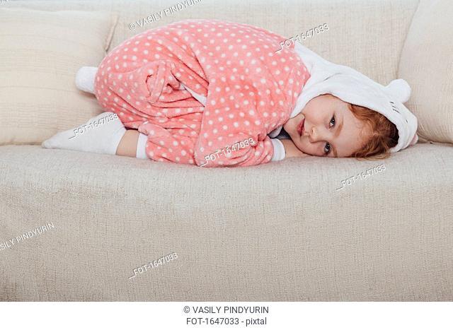 Portrait of smiling girl kneeling on sofa at home