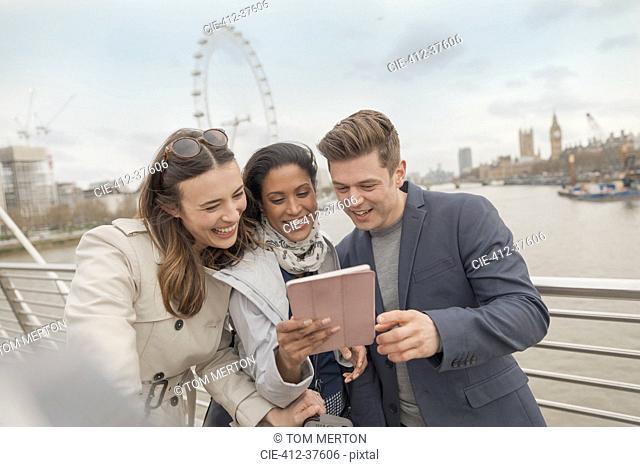 Friend tourists using digital tablet on bridge over Thames River, London, UK