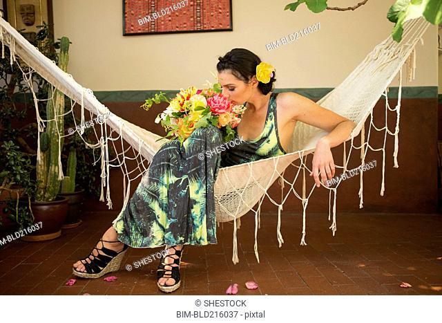 Woman smelling bouquet of flowers in hammock