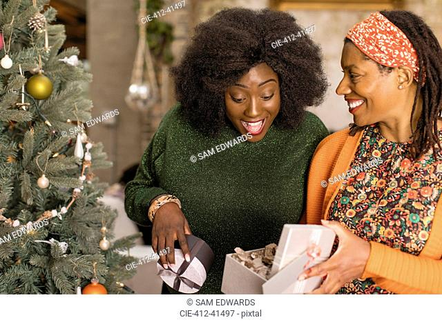 Mother surprising daughter with gift next to Christmas tree
