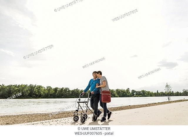 Senior man strolling with daughter at riverside