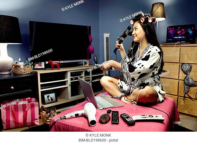 Filipino woman surrounded by gadgets curling her hair