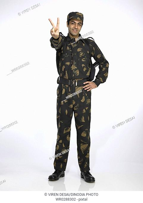 Indian army soldier standing in relaxed position showing victory sign MR702A