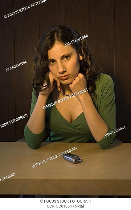 Hispanic businesswoman with cell phone on desk