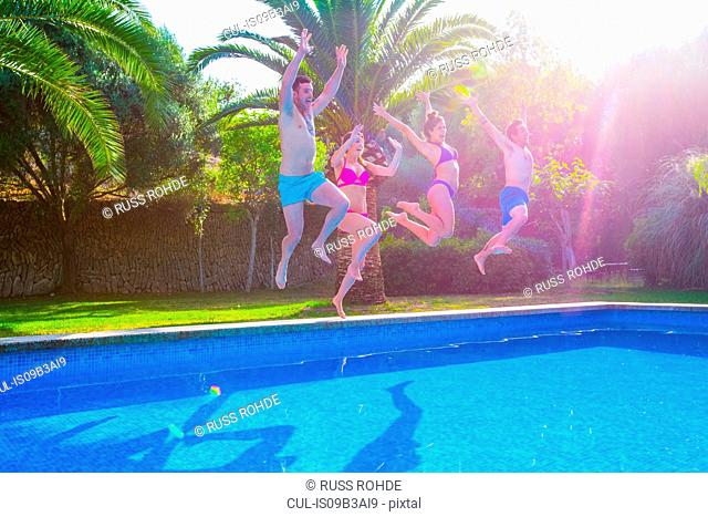 Friends jumping in swimming pool together