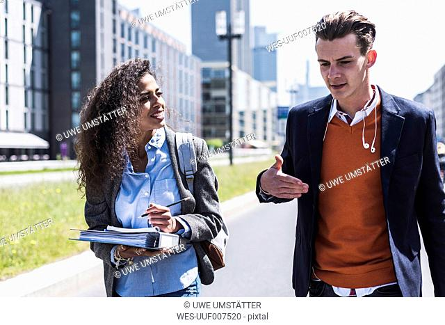 Young man and woman talking outdoors