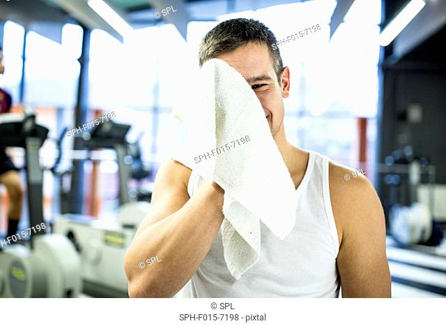 MODEL RELEASED. Portrait young man wiping his sweat with towel after exercising in gym