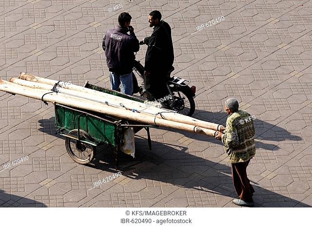Man pushing cart loaded with wooden beams, Djemaa el Fna, Marrakech, Morocco, Africa