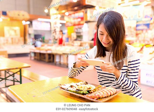Woman taking photo before having her assorted seafood