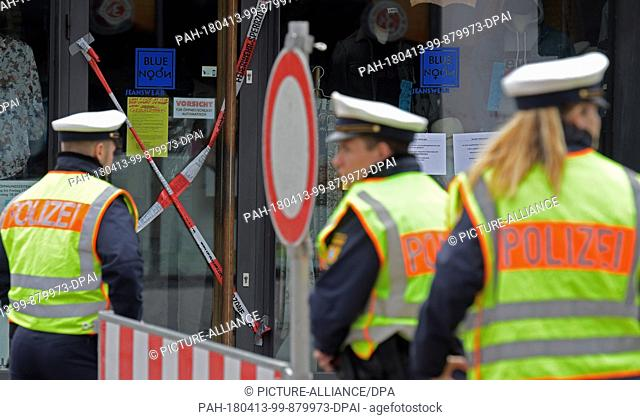 13 April 2018, Germany, Neu-Ulm: Police in front of a shop which has been cordoned off with warning tape. A 500kg bomb from the second world war was found at a...