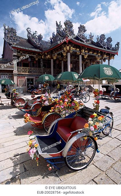 Koo Kongsi, the Dragon Mountain Hall. Exterior of clan house with line of decorated bicycle rickshaws in the foreground
