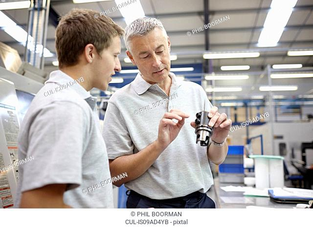 Manager and working looking at component in engineering factory