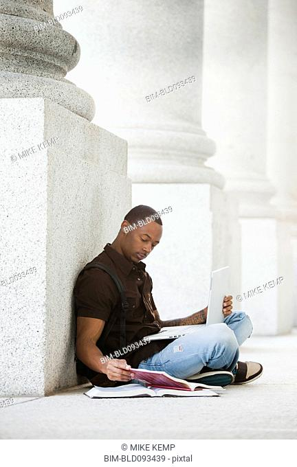 Black college student doing homework outdoors