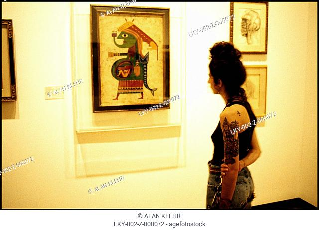 Tattooed woman stares at museum piece