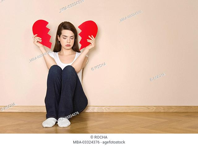 Woman holds divided heart in her hands, sits sadly on the floor