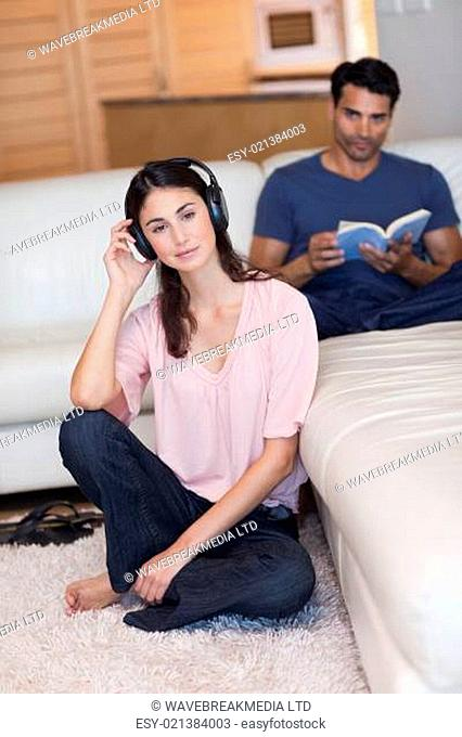 Portrait of a woman listening to music while her husband is reading a book