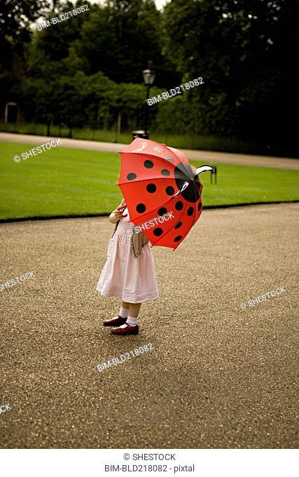 Girl standing under umbrella in park