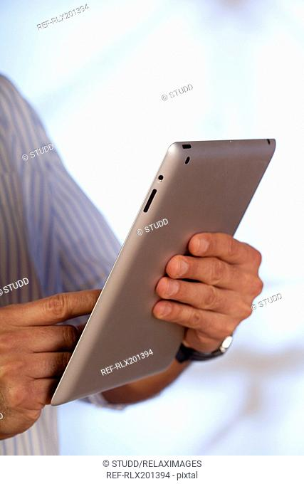man using Tablet PC iPad holding close up detail