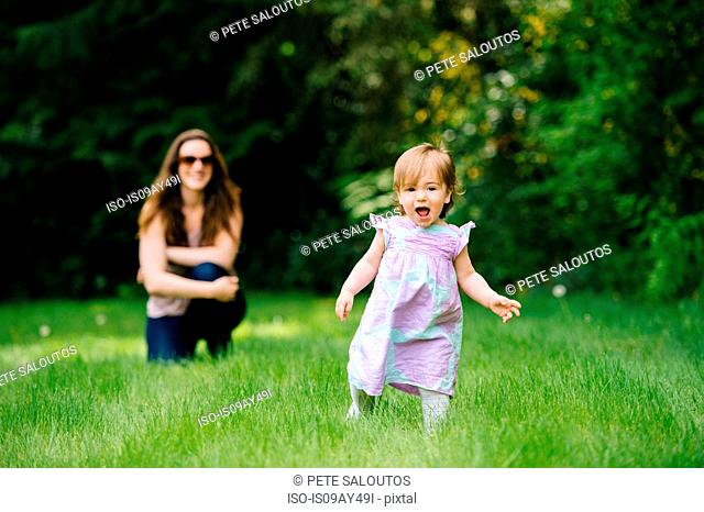 Female toddler running away from watching mother in park