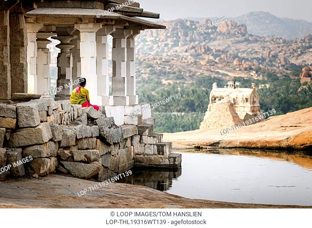 A woman sitting in some ancient ruins in Hampi