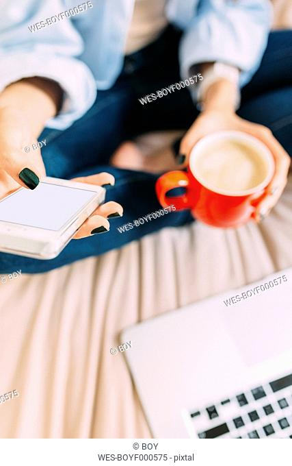 Young woman sitting on bed, coffee cup, laptop and smartphone