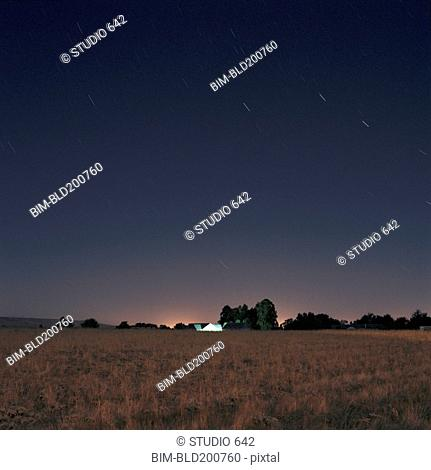 Stars and sunset over field