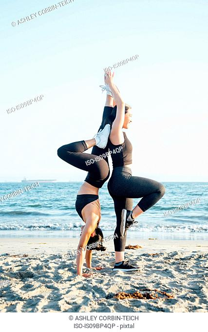 Friends doing exercises on beach