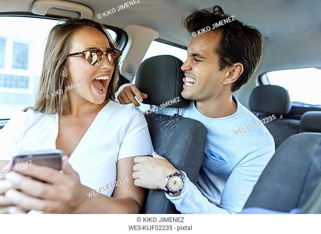 Happy couple in car grimacing with man on back seat and woman on front passenger seat