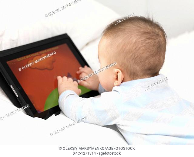Six month old baby boy playing with Apple iPad tablet computer