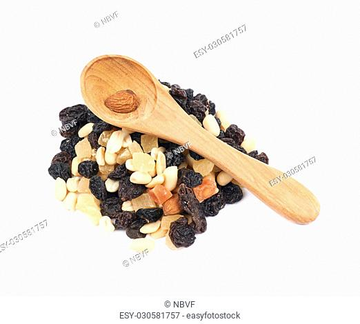 Pile of mixed nuts and dried fruits with the wooden spoon over it, composition isolated over the white background
